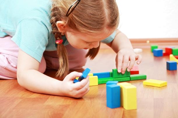 Adorable girl playing with blocks